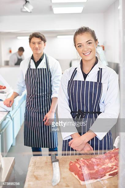 two young trainee butchers in a butcher's shop