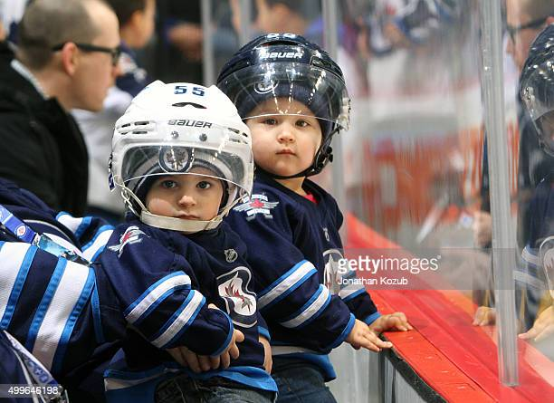 Two young Winnipeg Jets fans get up close to the action during the pregame warm up prior to NHL action between the Jets and the Toronto Maple Leafs...