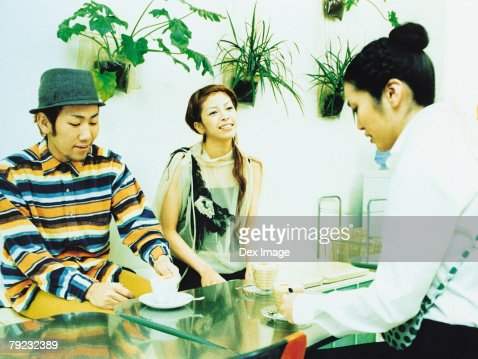 Two young woman and a man chatting and coffee : Stock Photo
