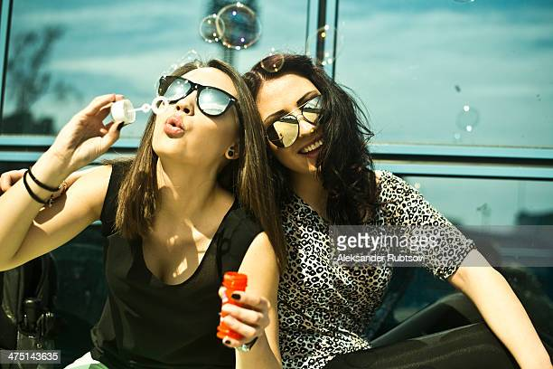 Two young woman blowing bubbles