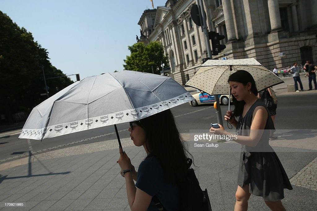 Two young woman carry umbrellas on a scorching hot summer day in the city center on June 20, 2013 in Berlin, Germany. Central Europe is in the grips of a heat wave in which temperatures in some regions have reached up to 38 degrees celsius.