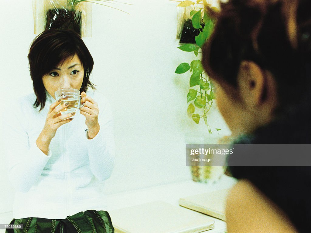 Two young woman chatting and drinking : Stock Photo