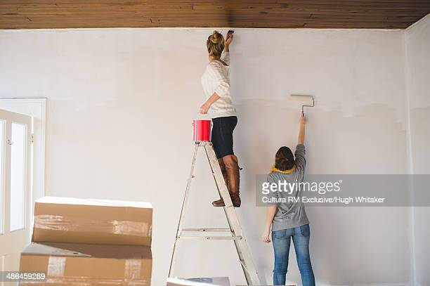 Two young woman decorating new home