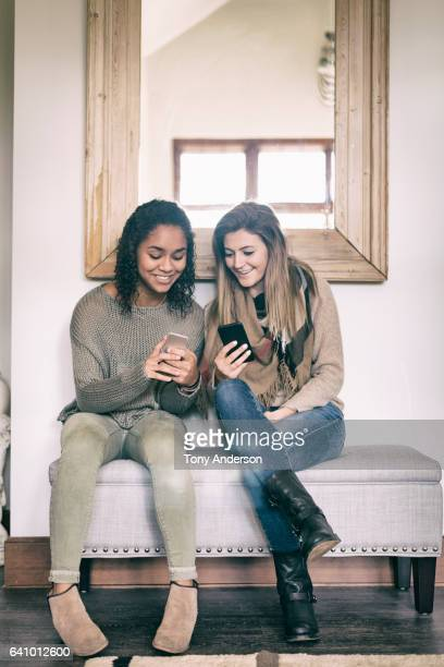 Two young woman friends looking at phones together indoors