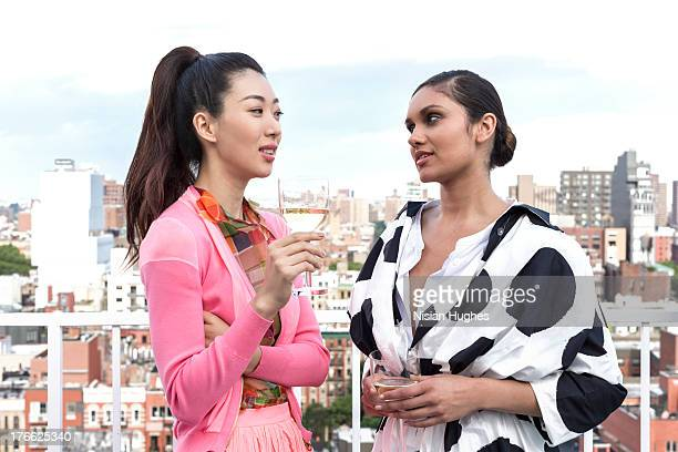 two young woman having a glass of wine on rooftop