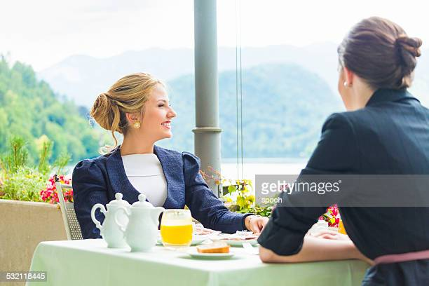 Two young woman having business lunch on restaurant terrace