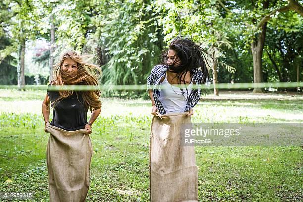 Two young woman having fun playing sack race