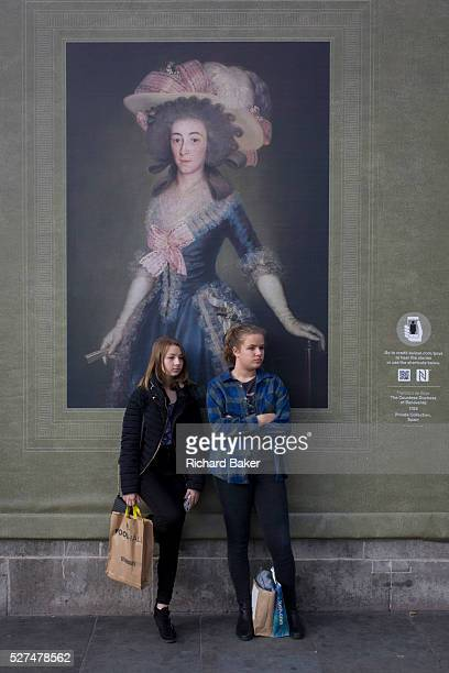 Two young woman listen to a busker beneath a portrait of the CountessDuchess of Benavente by Francesco Goya work sponsored by Credit Suisse and...