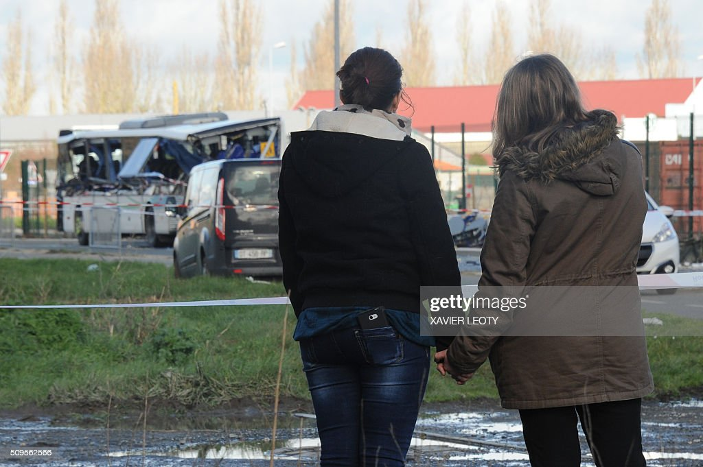 Two young woman look at the wreckage of a school minibus after it crashed with truck near Rochefort on February 11, 2016, killing at least six children. The head-on smash with a lorry carrying rubble came around 7:15 am (0615 GMT) near Rochefort in the western Charente-Maritime region. / AFP / XAVIER LEOTY