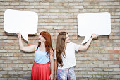 two young woman looking at speech bubbles