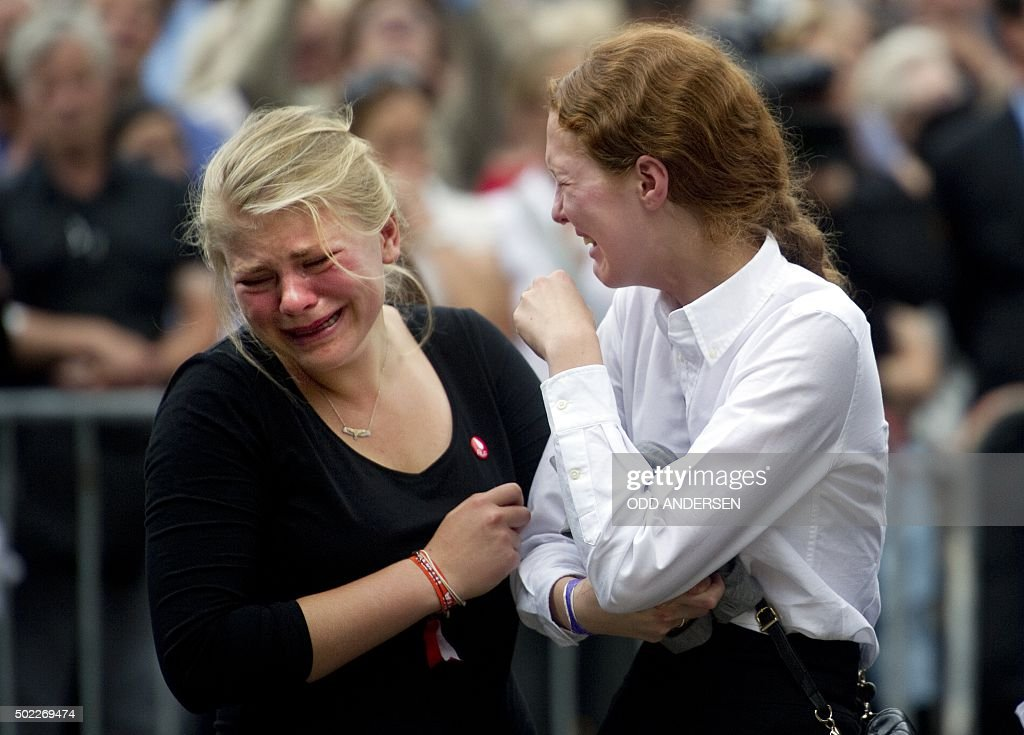 Two young woman mourn during a gathering on July 24 2011 in Oslo to pay tribute to the victims of a bomb explosion which ripped through government...