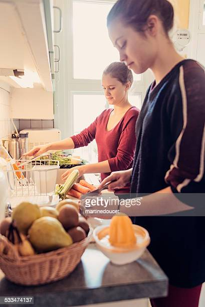 Two young woman preparing food on the kitchen cupboard.