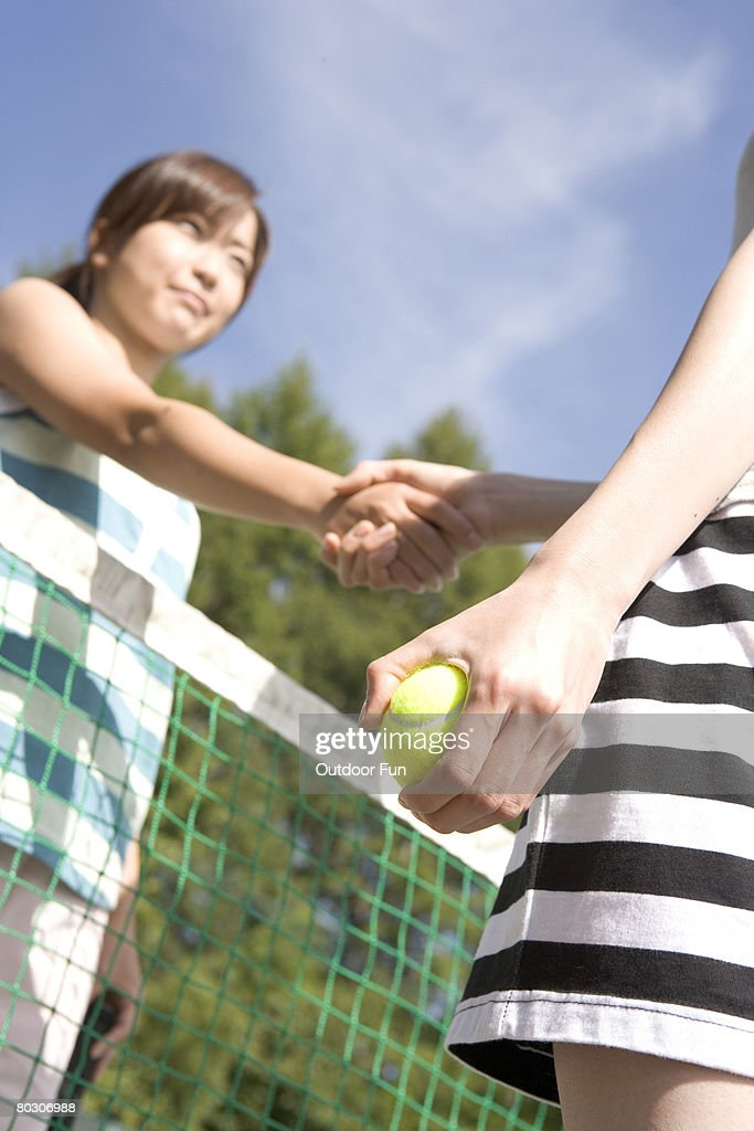 Two young woman shaking hands in tennis court, low angle : Stock Photo