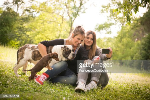 Two young woman taking photo with dog : Stock Photo