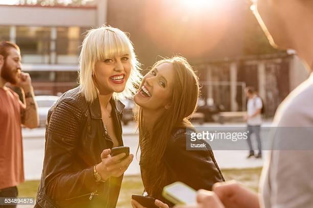Zwei junge Frau mit Smartphones im Freien