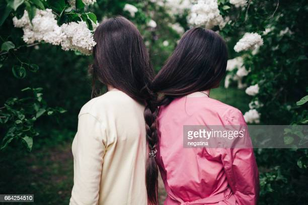 two young woman with long brown hair braided together standing shoulder to shoulder back to camera in blossoming lilac garden