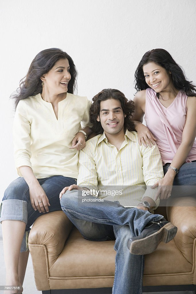 Two young women and a young man sitting together and smiling