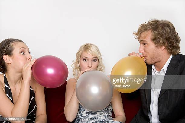 Two young women and man blowing up balloons, portrait