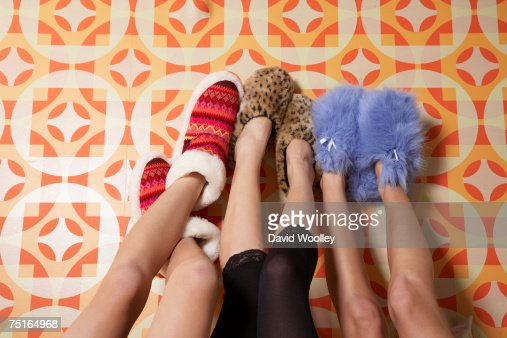 Two young women and teenage girl (16-17) wearing slippers, feet up against wall, low section : Stock Photo