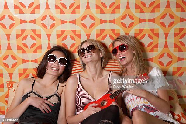 Two young women and teenage girl (16-17) wearing sunglasses, laughing