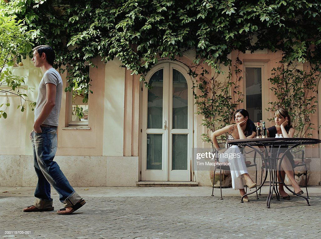 Two young women at cafe table watching man walk by : Stock Photo