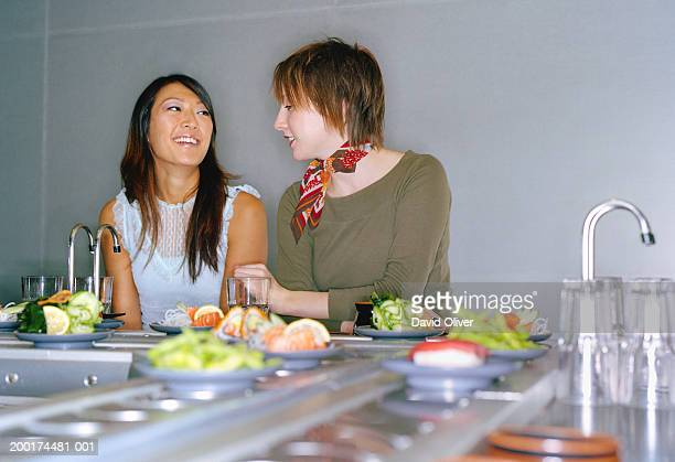 Two young women at sushi bar, smiling