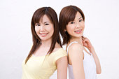 Two young women, back to back, smiling, front view