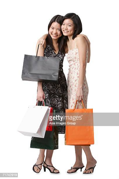Two young women carrying shopping bags, embracing, looking at camera