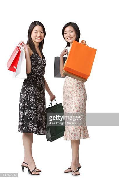 Two young women carrying shopping bags, looking at camera