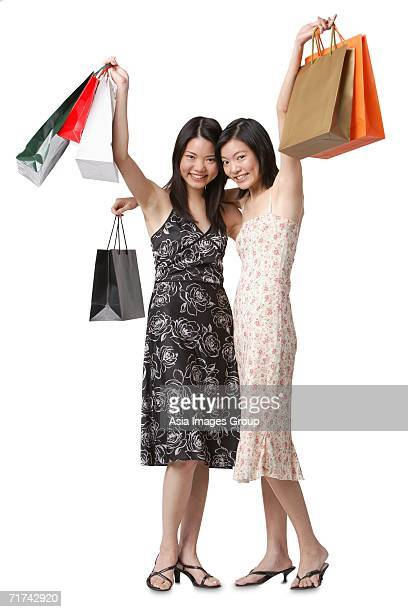 Two young women carrying shopping bags, smiling at camera