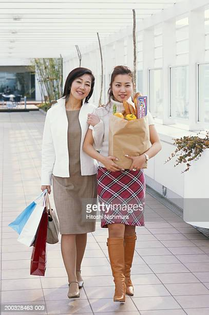 Two young women carrying shopping bags, walking arm in arm in corridor