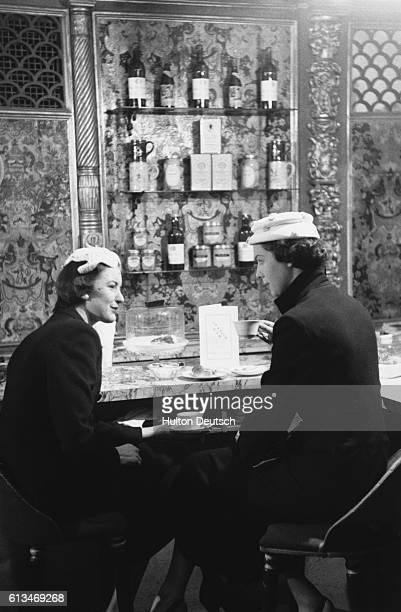 Two young women chat over a cup of coffee at an Italian style coffee bar