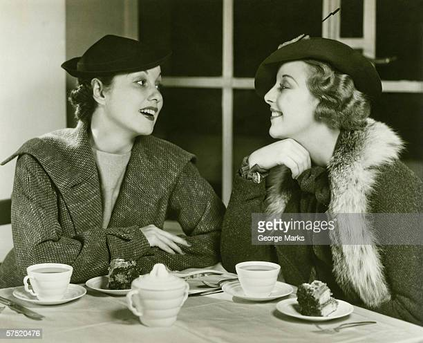 Two young women chatting, having coffee and cake, (B&W)