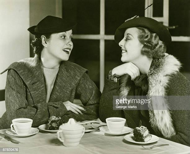 Deux jeunes femmes d'avoir une conversation, un café et une part de gâteau, (B & W