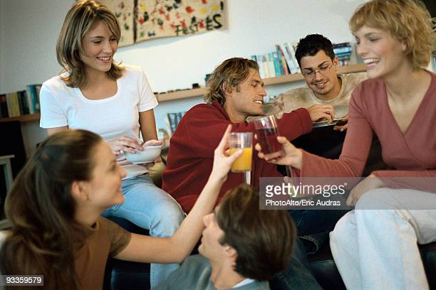 Two young women clinking glasses at home gathering of friends