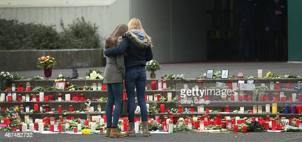 Two young women comfort one another while looking at flowers and candles left by mourners at the JosephKoenigGymnasium high school to pay tribute to...