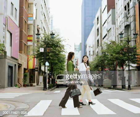 Two young women crossing urban street, having conversation, side view : Stock Photo