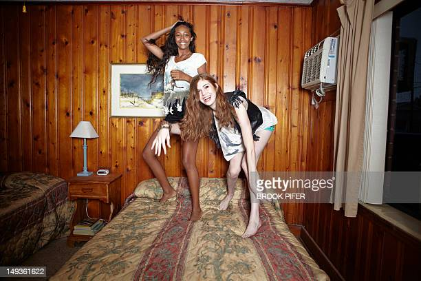 Two young women dancing on bed