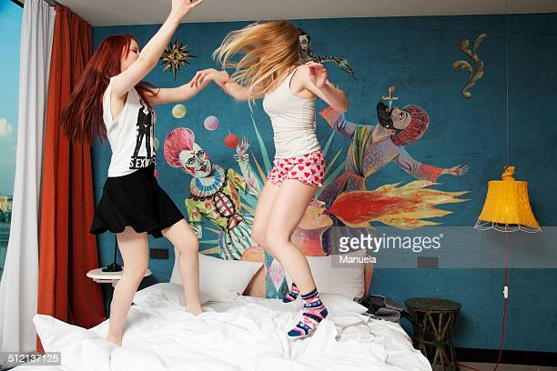 Two young women dancing on hotel bed