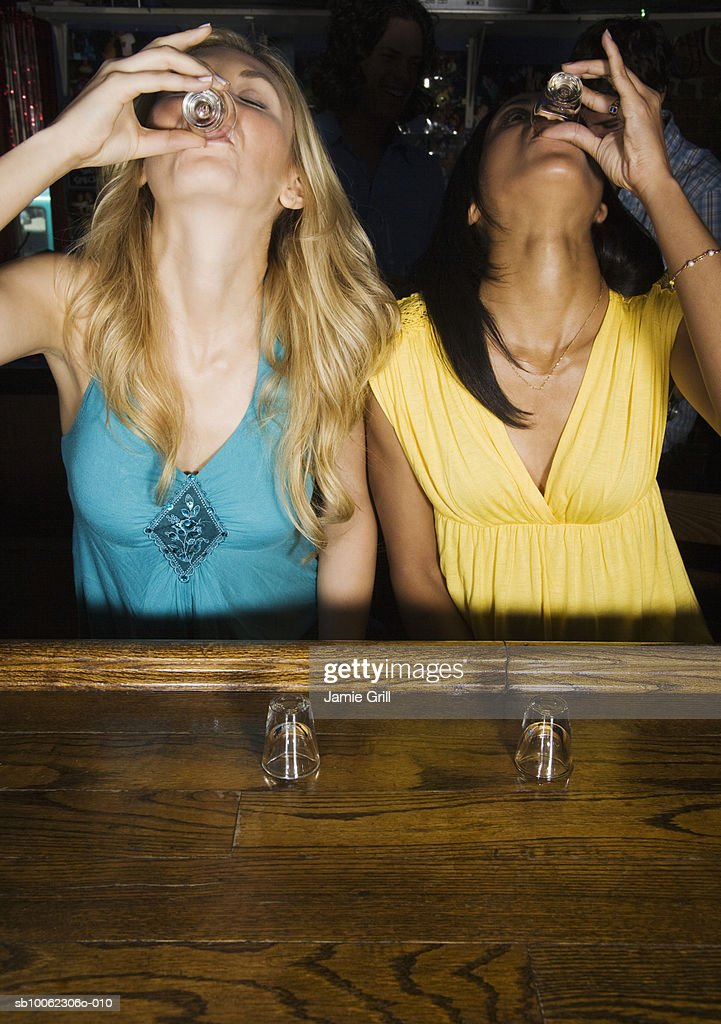 Two young women doing shots at bar : Stock Photo