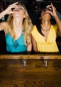 Two young women doing shots at bar