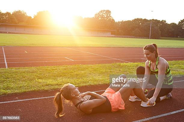 Two young women doing sit up training at race track