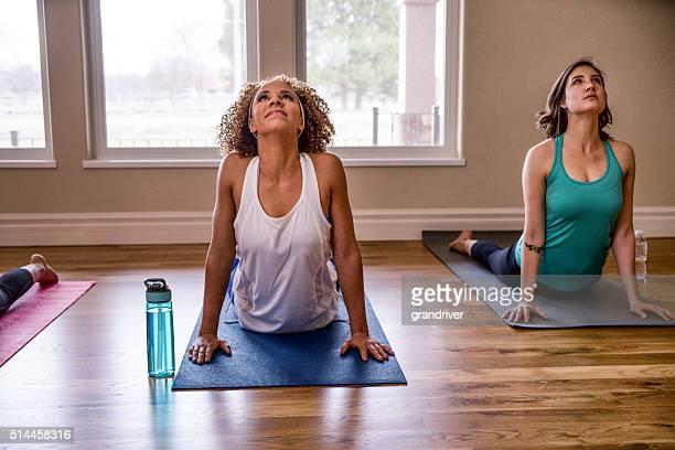 Two Young Women Doing Yoga Cobra Pose