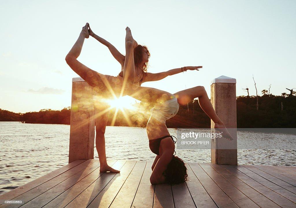 Two young women doing yoga on dock