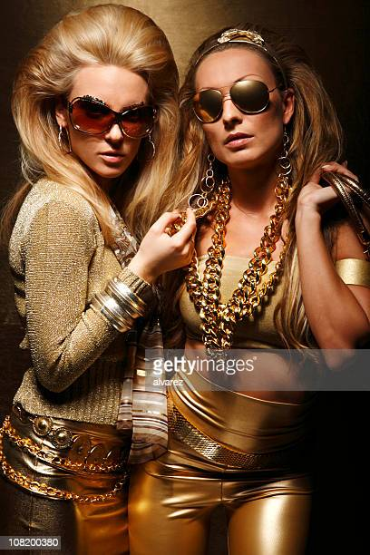 Two Young Women Dressed in All Gold Clothing Posing