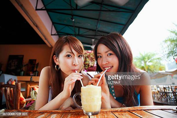 Two young women drinking cocktail in bar, portrait