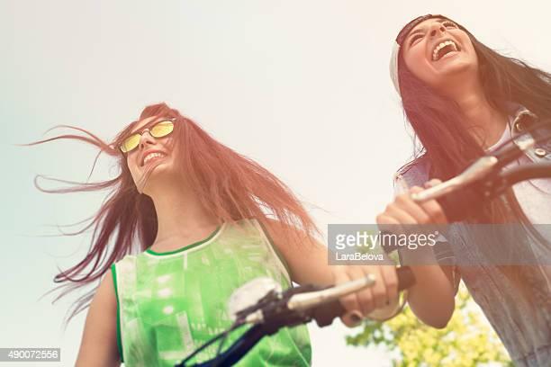 Zwei junge Frauen, die ein Fahrrad fahren