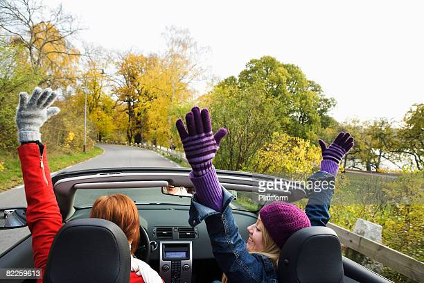 Two young women driving a cabriolet an autumn day Sweden.