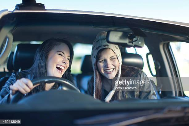 Two young women driving car