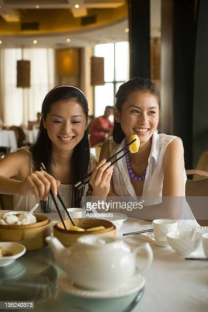 Two young women eating dim sum in a restaurant